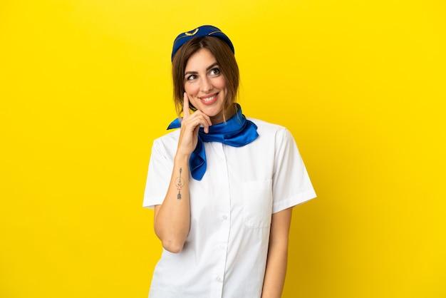 見上げながらアイデアを考えて黄色の背景に分離された飛行機のスチュワーデスの女性