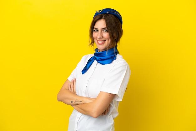 腕を組んで、楽しみにして黄色の背景に分離された飛行機のスチュワーデスの女性