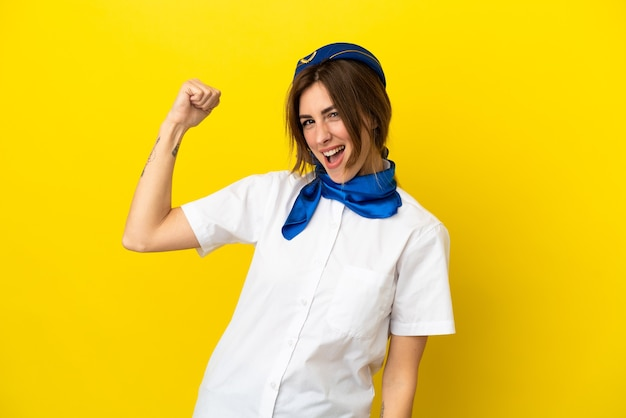 Airplane stewardess woman isolated on yellow background doing strong gesture
