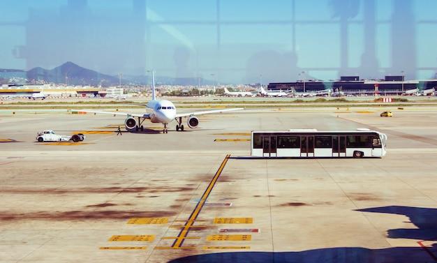 활주로에 정차한 비행기와 공항 터미널로 승객을 태운 버스
