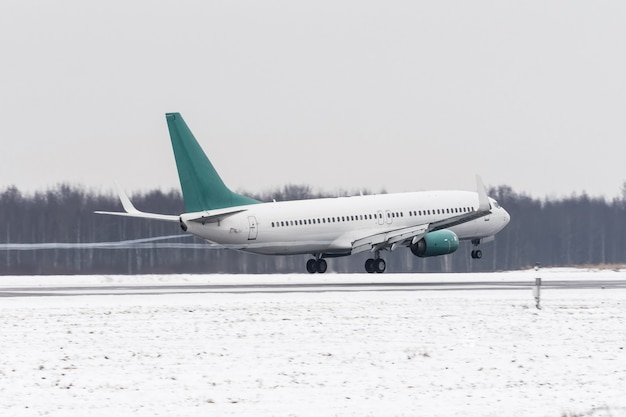Airplane take off from the snow-covered runway airport in bad weather during a snow storm, a strong wind in the winter.