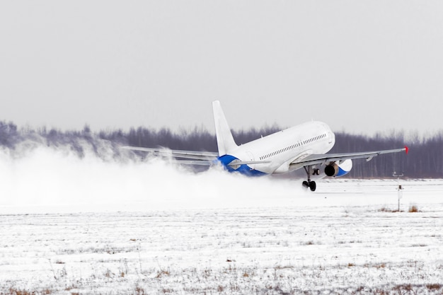 Airplane take off from the snow-covered runway airport in bad weather during a snow storm
