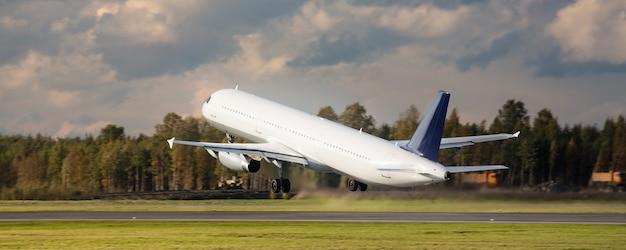飛行機は日中に空港から滑走路を離陸します、背面図。航空、輸送、旅行。