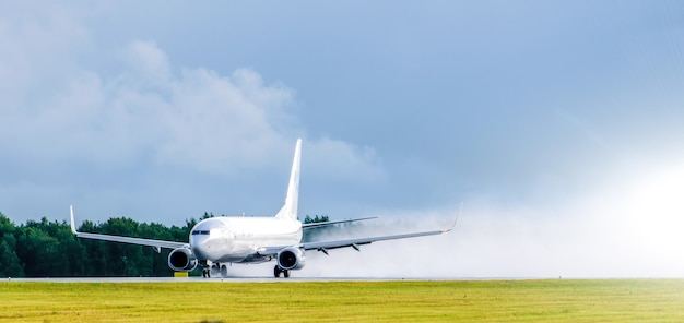 Airplane takes off at the airport rain splashes bad weather.