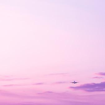 Самолет взлетает и поднимается высоко в концепции отпуска фиолетового закатного неба