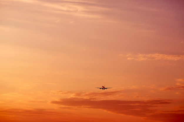 Airplane taking off and flying high in sunset sky vacation concept
