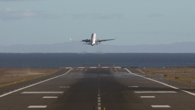Airplane taking off and flying over the sea