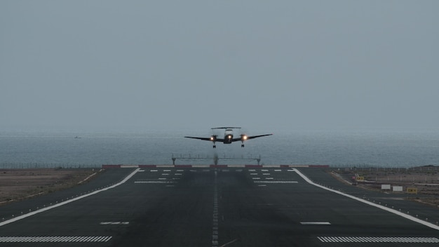 Airplane taking off from airport by the ocean
