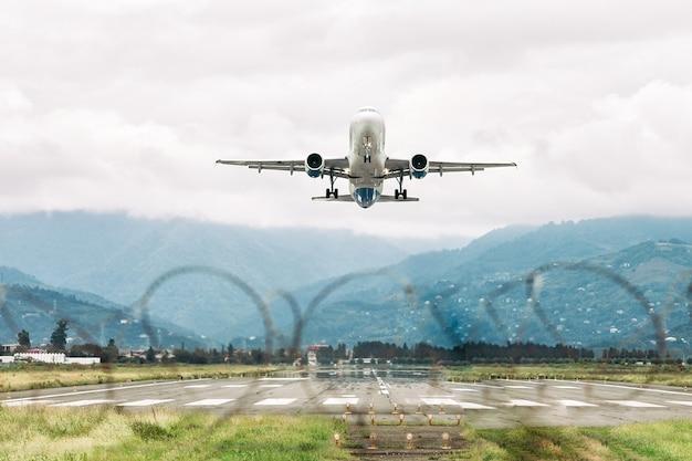 空を背景に空港から離陸する飛行機