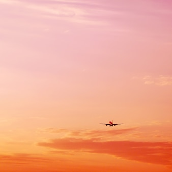 Airplane taking off and rising high in pink sunset sky vacation concept