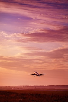 Airplane taking off at the sunset sky, silhouette of aircraft in the sky