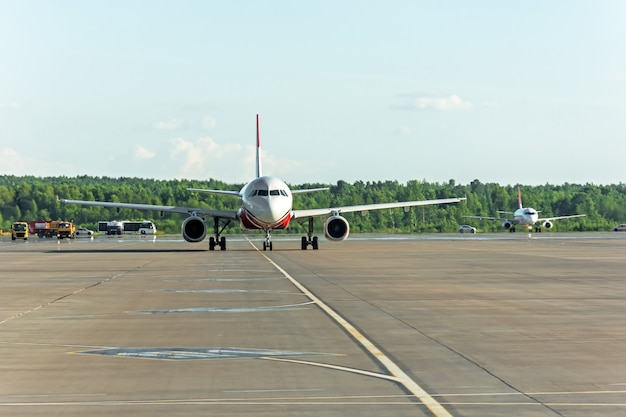 Airplane taxiing on the apron of the airport on the asphalt is visible marking.