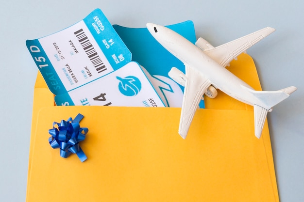 Airplane tickets in document case near toy aircraft