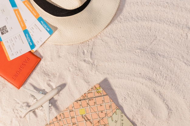 Airplane and tickets with hat and map on sand
