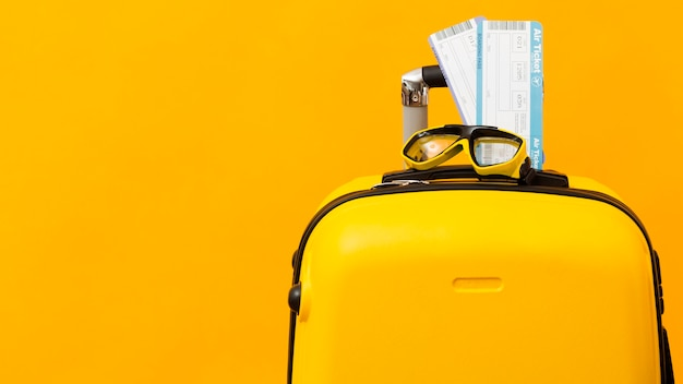 Airplane tickets on yellow luggage