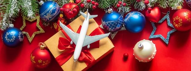 Игрушка в виде самолета над подарочной коробкой с рождественским украшением на ветке дерева