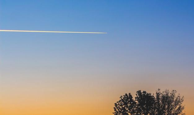 日没時の美しい空の飛行機のトレース_