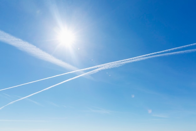 Airplane tracks and chemical trails in the clear blue sky.