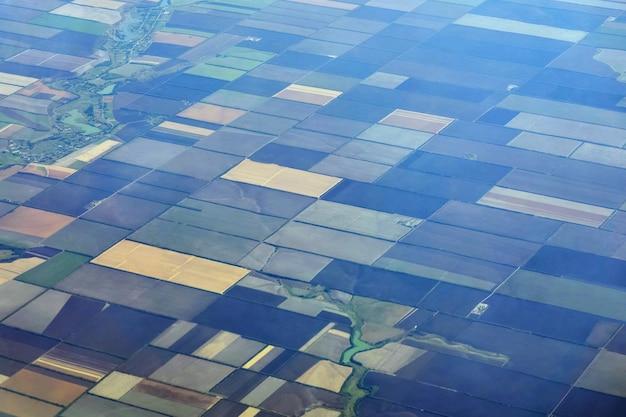 色とりどりの長方形のフィールドを持つ農業地域の飛行機のビュー