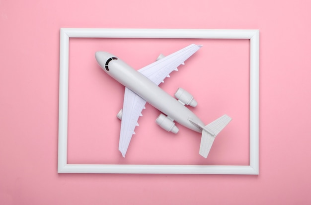 Airplane in a white frame on pink surface