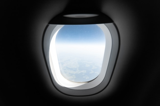 Airplane window view to cloudy sky and earth