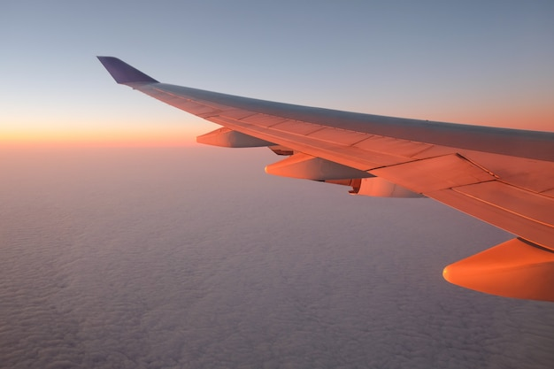 Airplane window view at sunset for vacation concept