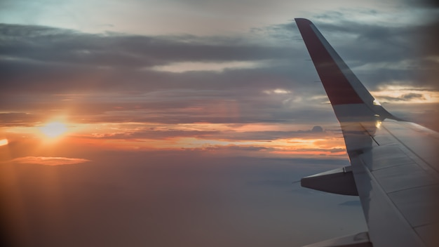 Airplane window view with wing at sunrise.