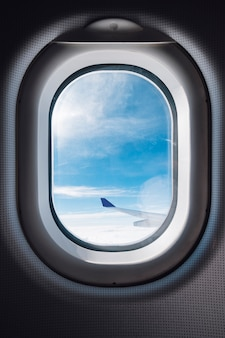 Airplane window with blue sky and wing