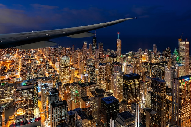 Airplane wing over the aerial view of chicago cityscape skyscraper under the blue sky at beautiful twilight time in chicago, illinois, united states, landscape and modern architecture concept