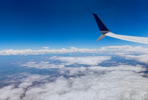 Airplane wing of airplane flying above the clouds in the sky view out the window on the cloudy sky the earth background