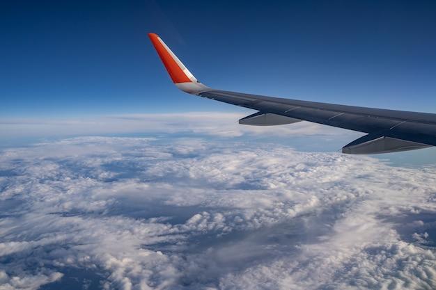 飛行機の翼の青い空と多くの白い雲が信じられないほどの高さで海外旅行