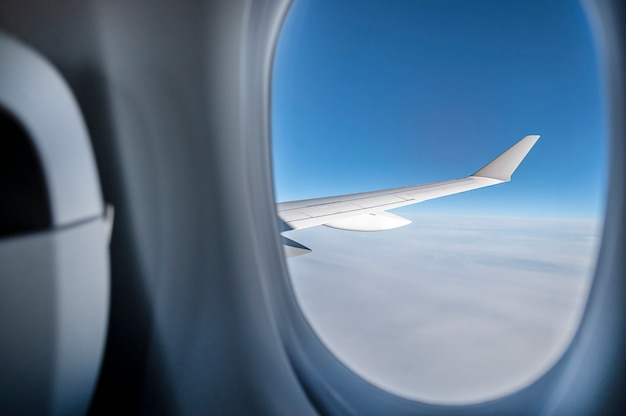 Airplane wing in blue sky through window