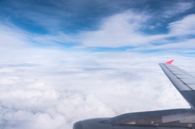 Airplane wing in the blue sky with clouds