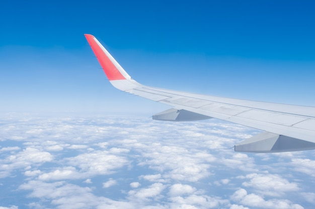 Airplane wing, clouds and blue sky has seen through the window of an aircraft view.