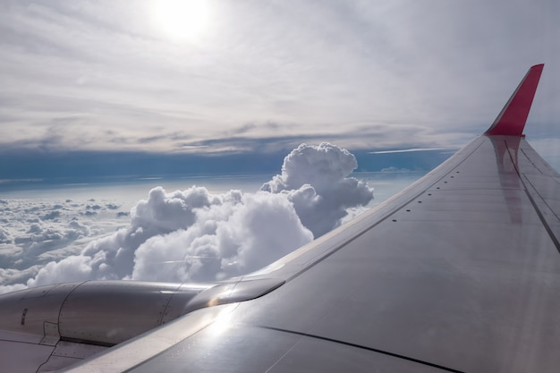 Airplane wing flying on clouds in sky