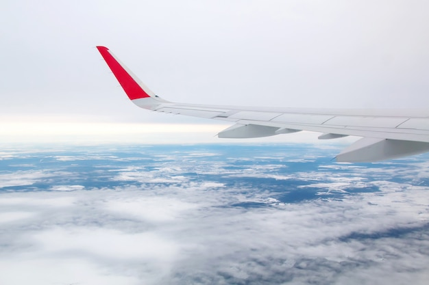 Airplane wing flying above the clouds