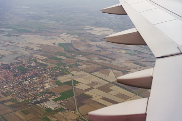 Airplane wing flying in the sky over fields and houses