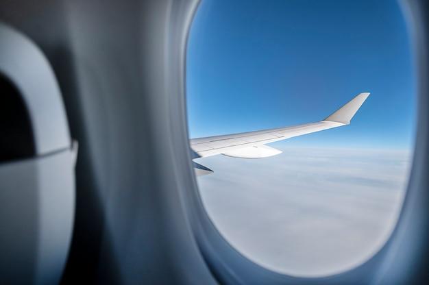 窓から青い空に飛行機の翼