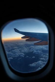 日没時の雲の上の舷窓の飛行機の翼。