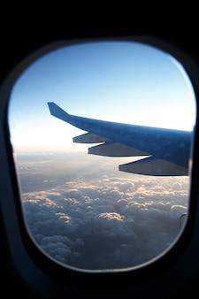 Крыло самолета в иллюминаторе над облаками на закате.