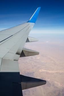 青い空を背景に空中の飛行機の翼