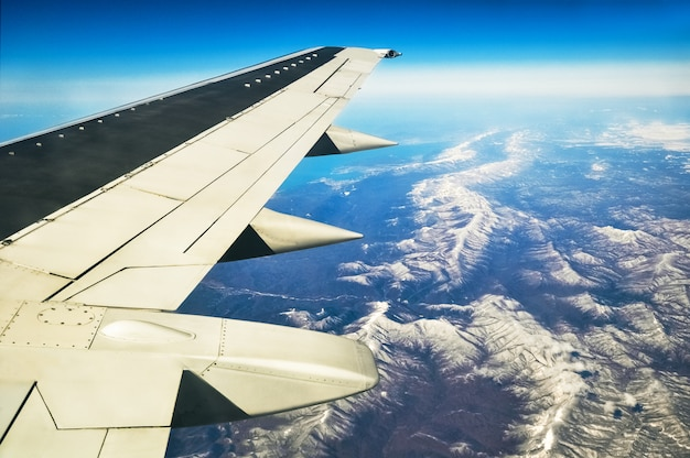 Airplane wing at mountain panoramic mountains landscape and blue sky background at summer day. travel destination