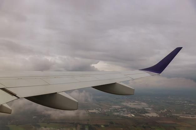 空の雲の上を飛んでいる飛行機の飛行機の翼は曇り空の窓の外を見る