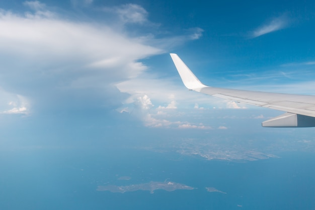 Airplane wing view out of the window the cloudy sky background, travel and holiday vacation concept