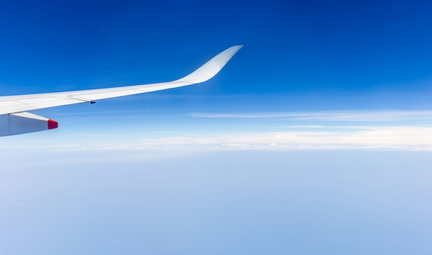 Airplane wing view out of the window the cloudy sky background