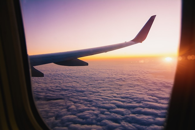 Airplane wing with sunrise in light flare by looking through the airplane window. - image
