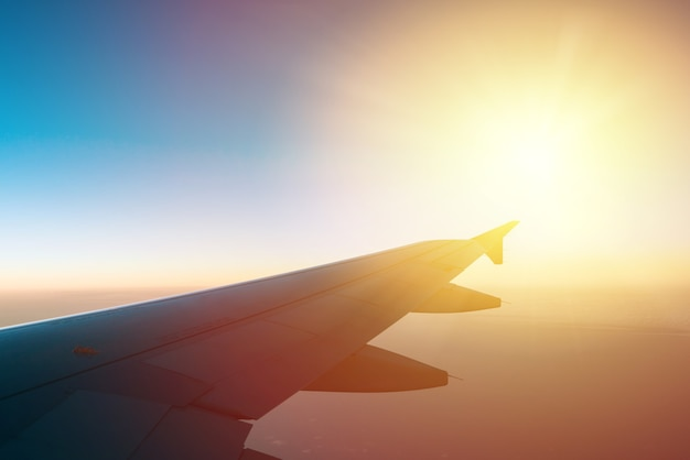 Airplane wing with sunrise in light flare