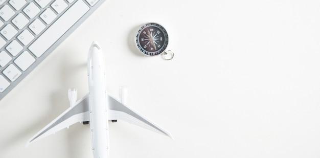 컴퓨터 키보드와 나침반 비행기입니다. 온라인 예약