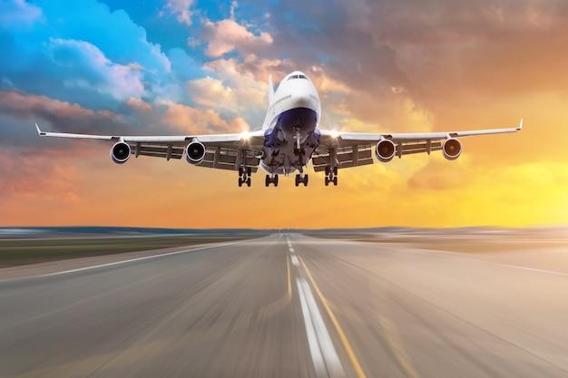 4개의 엔진이 달린 비행기가 저녁에 밝은 붉은 노을이 지는 동안 활주로에 착륙합니다.