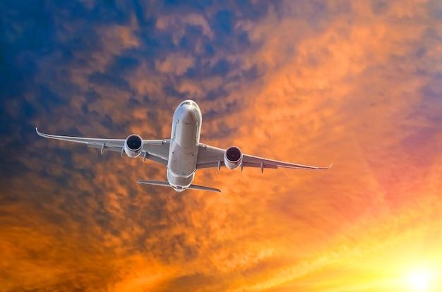 일몰에 활주로를 이륙한 후 조명이 켜진 비행기.